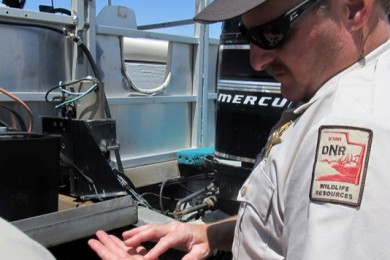 Division of Wildlife Resources Lt. Scott Dalebout examines a dead quagga mussel found on a boat at a watercraft checkpoint on U.S. Highway 89 near Big Water, Utah, May 13, 2015 | Photo by Heather Talley, courtesy of DWR, St. George News